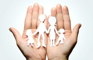 open hands holding with a paper cutout of a family holding hands