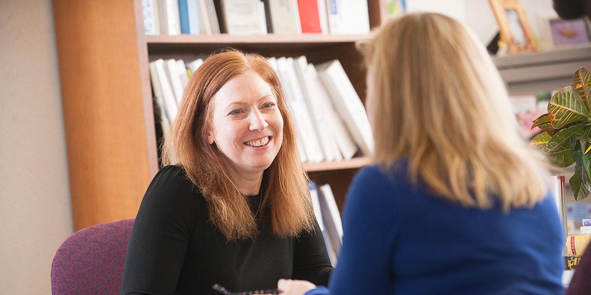 Two women talking in front of a bookshelf